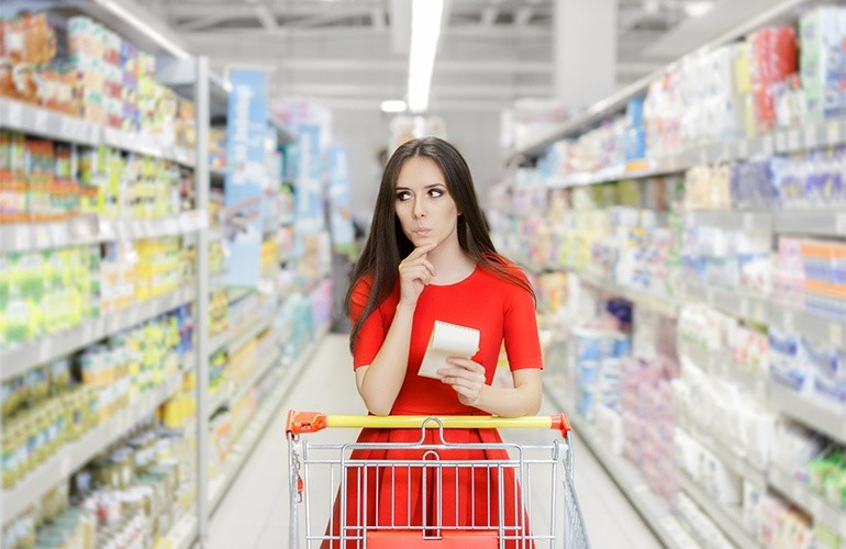 Девушка в магазине продуктов со списком
